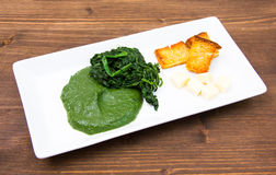 Tray with creamed spinach and croutons on wood Royalty Free Stock Photo