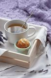 A tray with a cup of hot tea and cupcakes in bed with a knitted blanket. Herbal tea Hot drink Mood Love Message Breakfast in bed M. Orning Lifestyle stock image