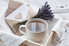 A tray with a cup of hot tea and lavender love letter in bed. Herbal tea Hot drink Mood Love Message Breakfast in bed Morning. Lifestyle stock images