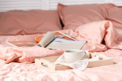 A tray with a cup of hot tea love letter and magazines in bed Stock Images