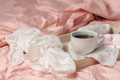 A tray with a cup of hot tea love letter and magazines in bed Royalty Free Stock Images