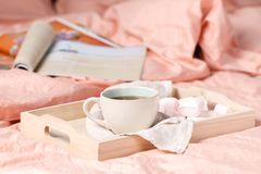 A tray with a cup of hot tea love letter and magazines in bed Royalty Free Stock Photos