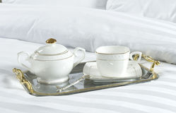 Tray with cup and sugar bowl on a bed Stock Images