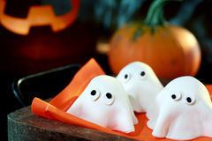 Tray of cute little Halloween monsters or ghosts. Made of pastry dough for a delicious party snack with a fresh pumpkin and glowing jack-o-lantern behind Royalty Free Stock Images