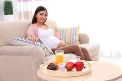 Tray with delicious breakfast and beautiful pregnant woman. On background Royalty Free Stock Photo