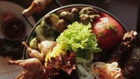 Tray with delicious grilled meat. Fresh lettuce, pickled onions and roasted vegetables stock video footage