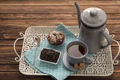 Tray with dry black tea leaves, cup of aromatic beverage and tasty muffin on table royalty free stock image