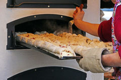 A tray of filled bread is pushed into the baking oven Stock Image