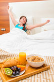 Tray of food in focus and stretches girl Royalty Free Stock Image