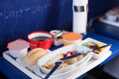 Tray of food on the plane. Focus on a plastic cruet stand with pancakes. Shallow depth of focus Stock Image