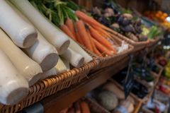 A tray of fresh leeks, carrots and other veggies at a farmers market in a wicker basket. stock photos
