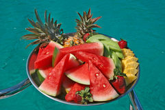 Tray of fruit. A tray of watermelon,pineapple and strawberries sliced and whole with the beautiful clear blue ocean in the bankground Stock Image