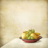 Tray with fruits on a table against a grunge wall. Grunge still life of a light interior, a table and a fruit tray stock photo
