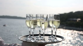 Tray glasses champagne hands waiter at background of sea at sunset.  stock footage