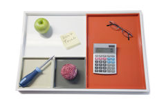 Tray with green apple, calculator, eyewear and other office supplies Royalty Free Stock Photo