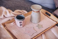 A tray with a jug and a mug. On a beige fabric Royalty Free Stock Photography