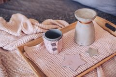 Tray with a jug and a mug on the cloth. In beige tones Royalty Free Stock Photo