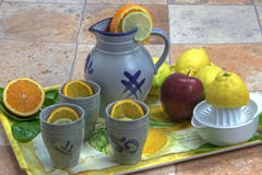 Tray with lemon juice. Tray with lemons, oranges, apple and a jug and mugs Stock Photos