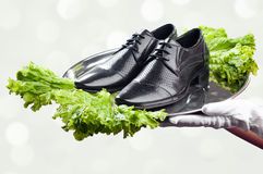 Tray with pair of male shoes in waiter's hands. Waiter's hands holding tray with pair of male shoes decorated with lettuce. Concept of fresh product immediately Royalty Free Stock Image