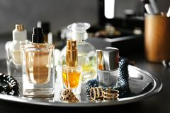 Tray with perfume bottles and accessories. On table Royalty Free Stock Photos