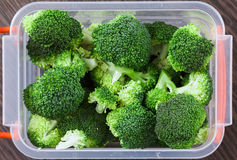 Tray with raw broccoli for freezing. Stocking up vegetables for winter storage in plastic container. Overhead view Stock Image