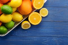 Tray with ripe citrus fruits on wooden background stock photo