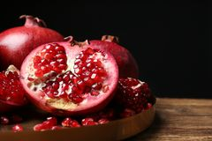 Tray with ripe pomegranates on table against black background stock images