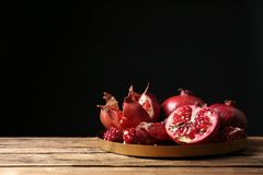 Tray with ripe pomegranates on table against black background royalty free stock images