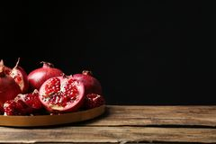 Tray with ripe pomegranates on table against black background stock photos