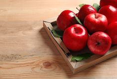 Tray with ripe red apples. On wooden background royalty free stock image
