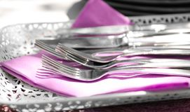 Tray with silver cutlery and lilac napkin on table. Closeup Stock Images