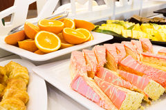 Tray of sliced cake with pink icing on a buffet Royalty Free Stock Photos