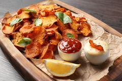 Tray with sweet potato chips and sauce on wooden table. Closeup stock images
