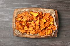 Tray with sweet potato chips on wooden table. Top view royalty free stock photos