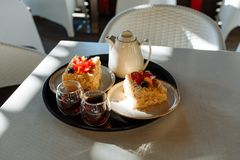 Tray with a teapot, cups and cakes on a table in a cafe stock images