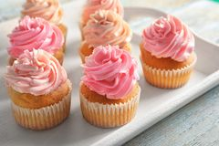 Tray with yummy cupcakes. On wooden table Royalty Free Stock Photography