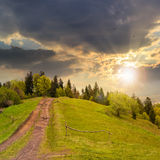 Trayectoria al bosque de la montaña en la puesta del sol Imágenes de archivo libres de regalías