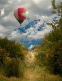 Trayectoria al globo del cielo-uno que vuela sobre el bosque y una trayectoria en un matorral de árboles Imagenes de archivo