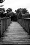 Trayectoria blanco y negro a través de un puente de madera Imagen de archivo
