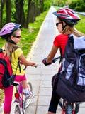 Trayectoria de la bicicleta con los niños Muchachas que llevan el casco con la mochila Fotografía de archivo libre de regalías