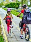 Trayectoria de la bicicleta con los niños Muchachas que llevan el casco con la mochila Imágenes de archivo libres de regalías