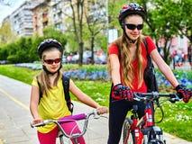 Trayectoria de la bicicleta con los niños Muchachas que llevan el casco con la mochila Foto de archivo