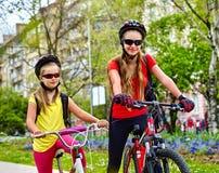 Trayectoria de la bicicleta con los niños Muchachas que llevan el casco con la mochila Fotos de archivo