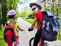 Trayectoria de la bicicleta con los niños Muchachas que llevan el casco con paseo del ciclyng de la mochila Fotos de archivo