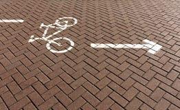 Trayectoria de la bicicleta en el pavimento rojo con la muestra Foto de archivo