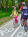 Trayectoria de la bicicleta para las muchachas del niño que llevan el casco con paseo del ciclyng de la mochila Fotos de archivo libres de regalías