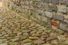 Trayectoria de piedra del adoquín a lo largo de la pared de ladrillo del grunge Fotos de archivo libres de regalías