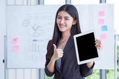 trayectoria de recortes en la pantalla negra, pulgar de la demostración de la mujer de negocios para arriba y sosteniendo la tabl foto de archivo libre de regalías