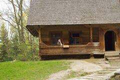 Trayectoria a dirigirse y casa de madera vieja con la mujer mayor y el gato foto de archivo libre de regalías
