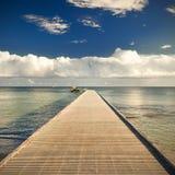 Trayectoria en el embarcadero por el océano con el cielo azul y las nubes Fotos de archivo libres de regalías